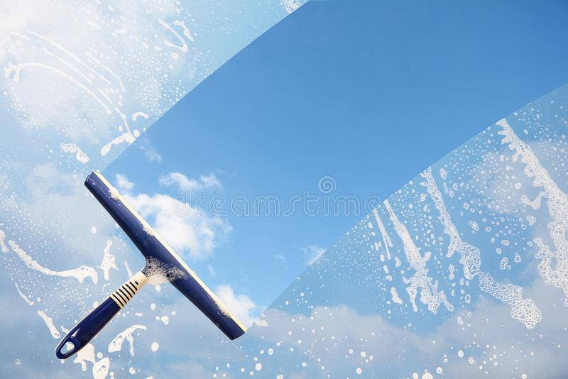 Rubber squeegee cleans a soaped window and clears a stripe of bl stock photos