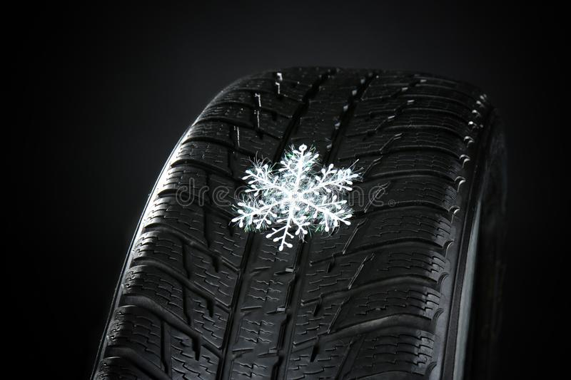 Rubber winter tire with snowflake on dark background, stock image