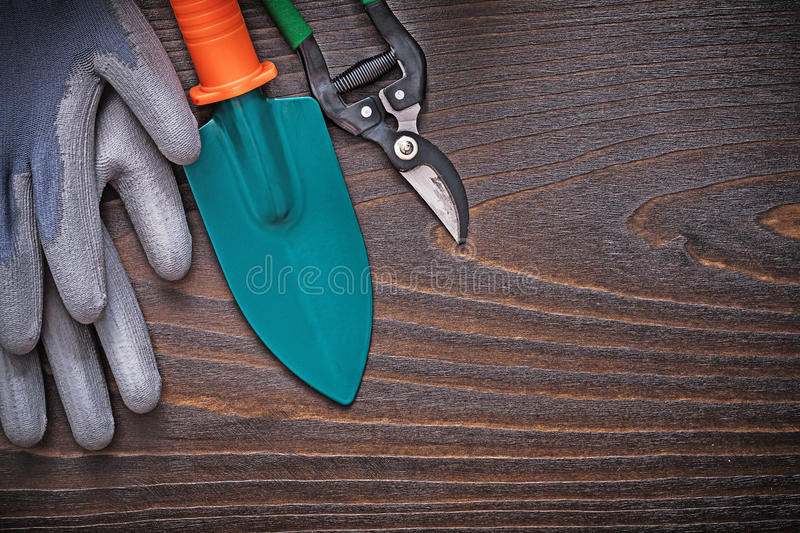 Rubber working gloves hand spade and secateurs on vintage wooden. Board agriculture concept royalty free stock image