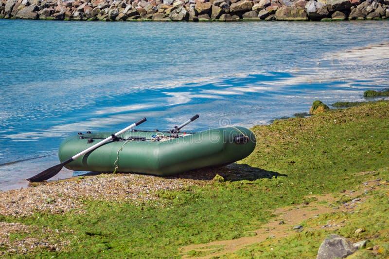 Rubberboot met vistuig die zich op een rivier dichtbij het zandige strand bevinden stock afbeelding