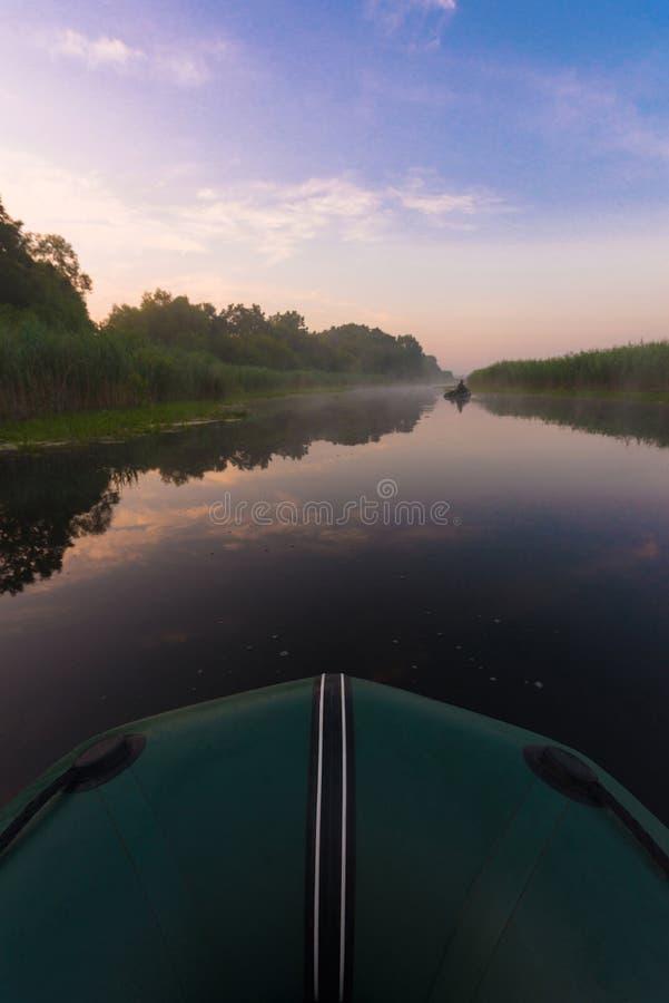 Rubberboot vroege ochtend op de rivier stock afbeelding
