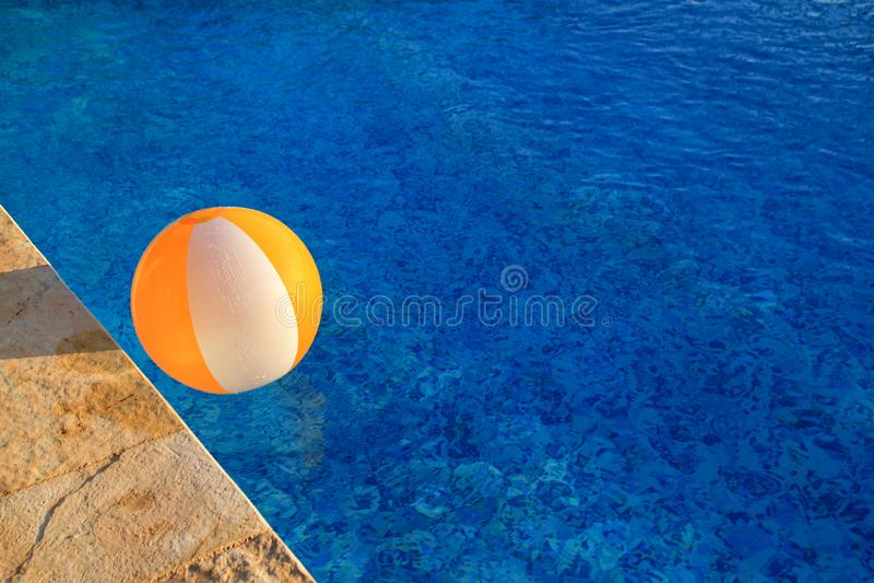 Rubberlucht geel wit opblaasbaar bal en stuk speelgoed voor zwembad in transparant blauw water Het Multi-colored strandbal drijve stock fotografie