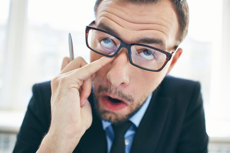 Rubbing eye. Face of funny businessman in eyeglasses rubbing eye stock photos