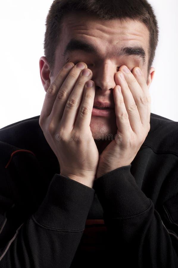 Rubbing eyes. Young man rubbing his eyes royalty free stock photos