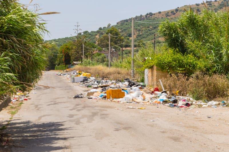 Rubbish ao longo de uma estrada secundária em uma vila imagens de stock
