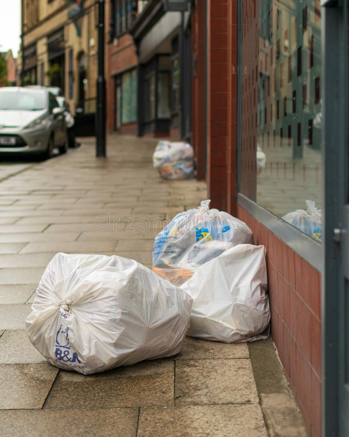Rubbish bags in the street. Wigan, United Kingdom - September 15 2019: A pile of rubbish on the street outside of the shops in Wigan royalty free stock photography