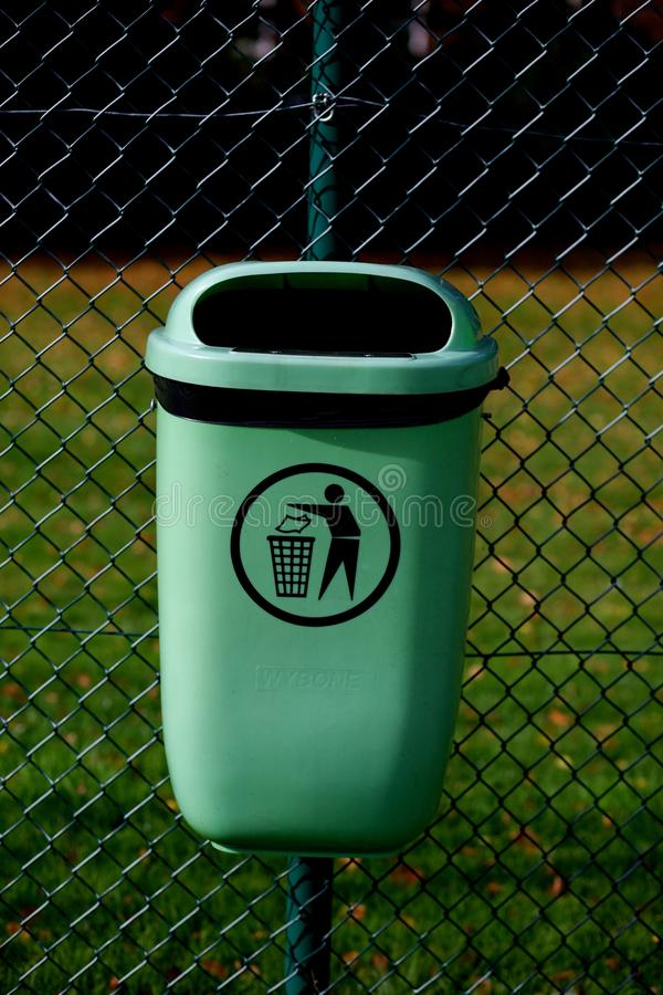 Rubbish bin on a wire fence. Small green plastic bin on sports court fence stock photography