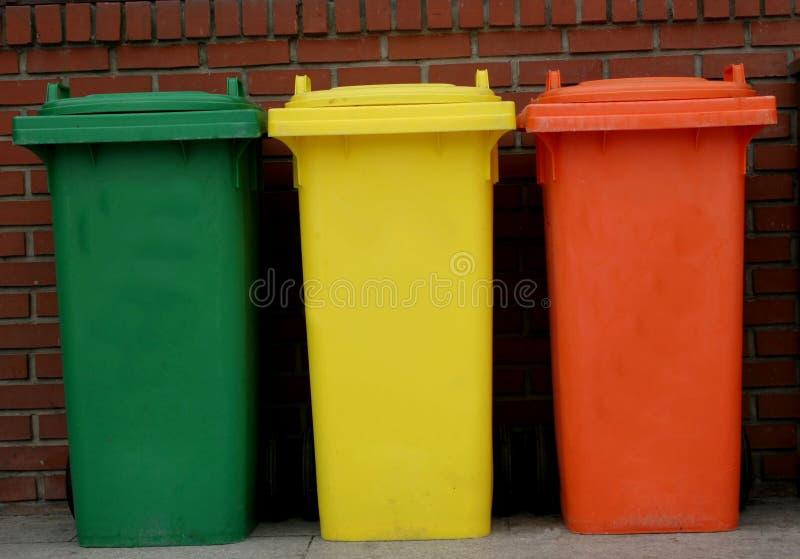 Rubbish bins. Green, yellow and orange rubbish bins in a row royalty free stock photography