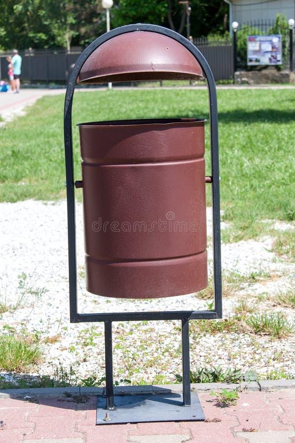 Rubbish o escaninho na rua um fundo da grama fotos de stock