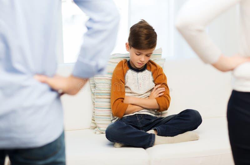 Rubbning eller pojke och föräldrar för känsla skyldig hemma fotografering för bildbyråer