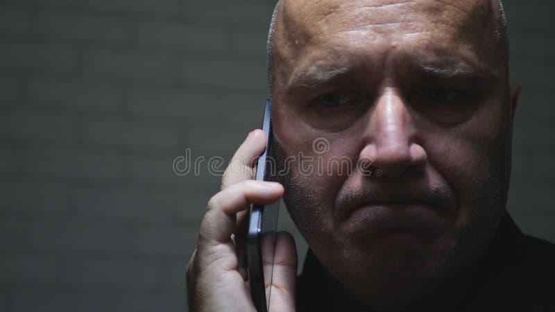 Rubbningaffärsman Trying som gör en påringning genom att använda mobilen arkivfoton