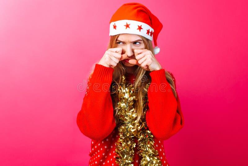Rubbningflickan i jultomten hatt och med glitter på hennes hals, gnider hennes ögon och önskar att gråta med harm på en röd bakgr royaltyfria bilder