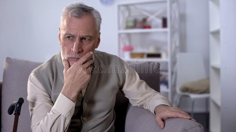 Rubbninggamal man som sitter på soffan som tänker över hälsoproblem, låga pensioner fotografering för bildbyråer