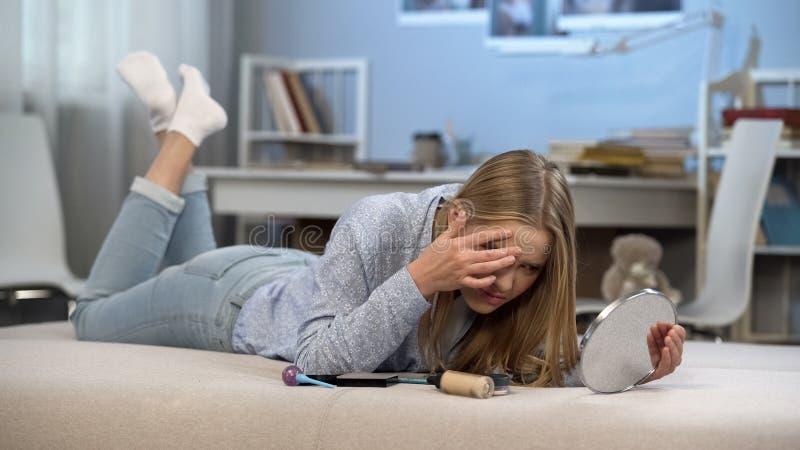 Rubbningtonåring med problemhud som ser i spegeln, pubertetålder, cosmetology royaltyfri foto