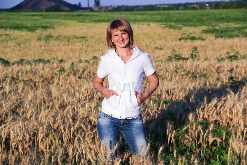 Rubia en jeans en un campo con trigo fotografía de archivo libre de regalías
