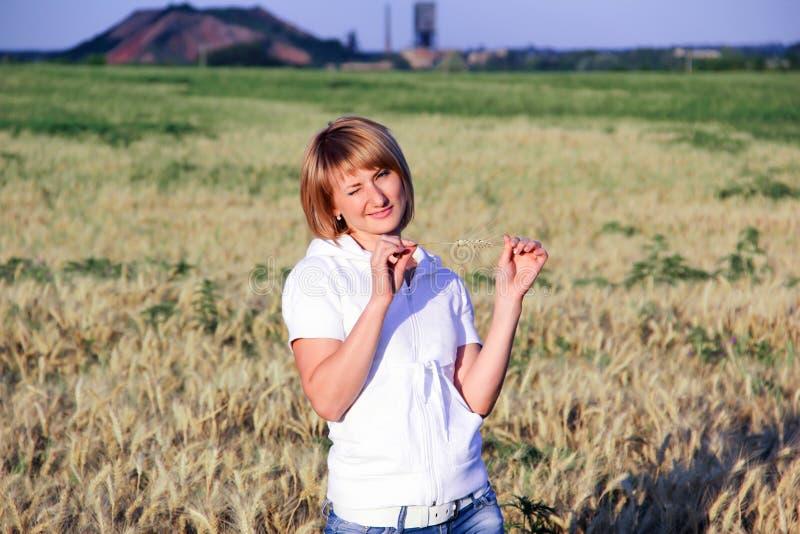 Rubia en jeans en un campo con trigo imágenes de archivo libres de regalías