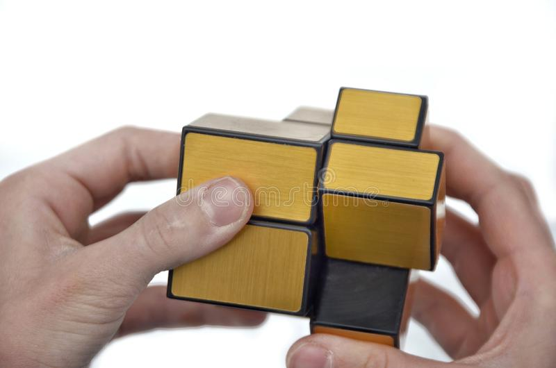 Rubik的立方体在孩子的手上,特写镜头,顶视图,白色木背景 女孩拿着Rubik的立方体和戏剧与它 免版税库存图片