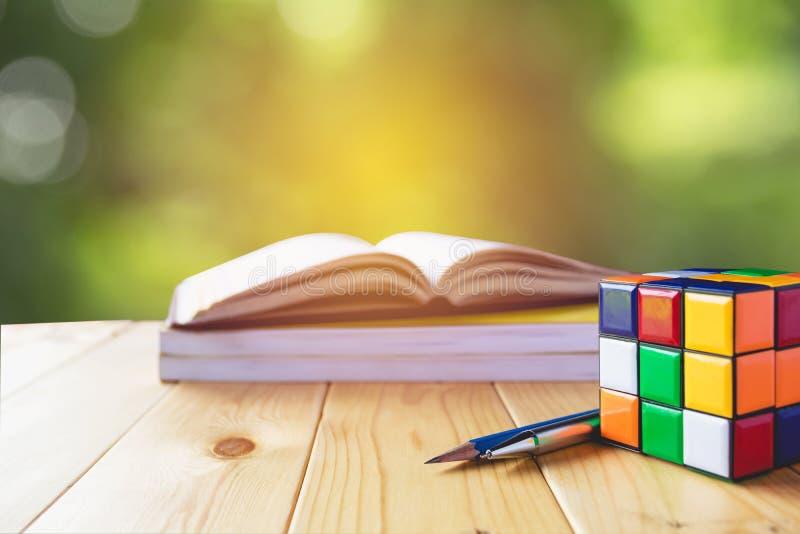 Rubik kub, bok, penna och blyertspenna i trätabell på naturen royaltyfri foto