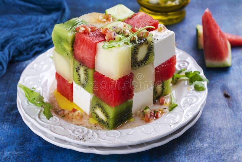 Rubik`s cube fruit salad. With watermelon, feta cheese, melon, kiwi and cucumber stock photography