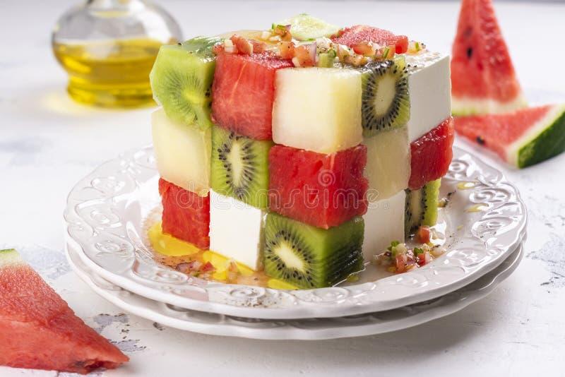 Rubik`s cube fruit salad. With watermelon, feta cheese, melon, kiwi and cucumber royalty free stock photo
