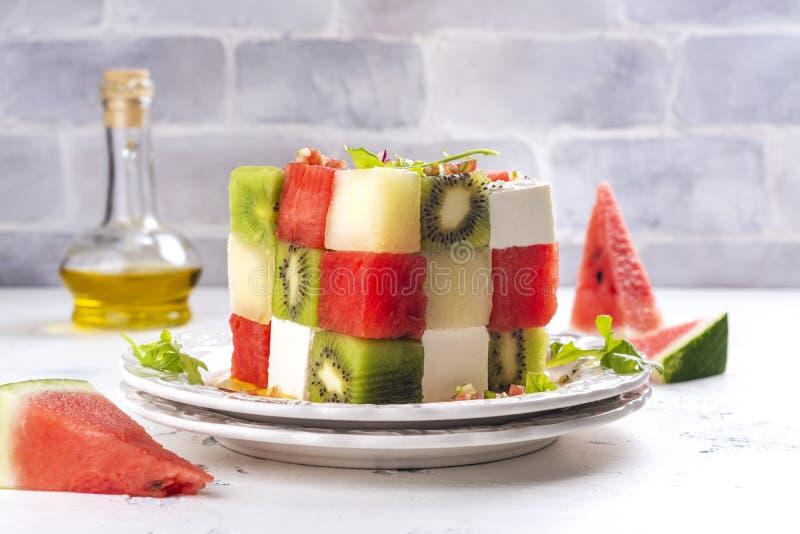 Rubik`s cube fruit salad. With watermelon, feta cheese, melon, kiwi and cucumber royalty free stock image