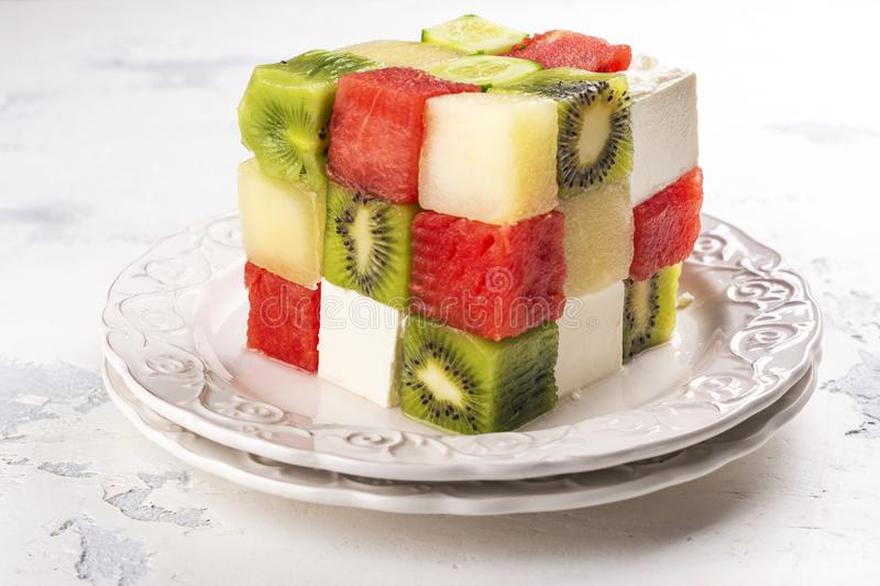 Rubik`s cube fruit salad. With watermelon, feta cheese, melon, kiwi and cucumber royalty free stock photography