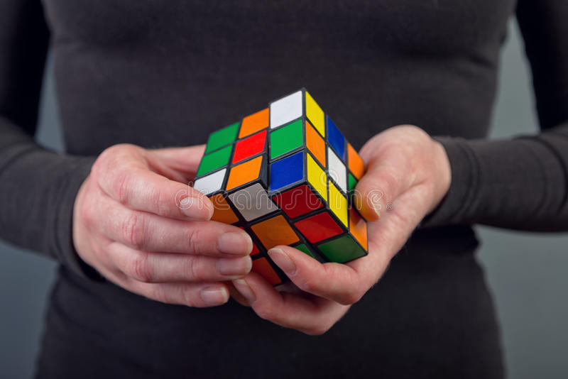 Rubik's Cube. NOVI SAD, SERBIA - NOVEMBER 17, 2014: Woman solving Rubik's Cube invented by a Hungarian architect Erno Rubik in 1974 is famous is 3 dimensional royalty free stock photo