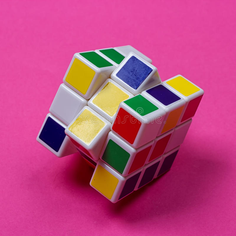 Rubik`s Cube on the pink. Kyiv, Ukraine - August 25th, 2017: Rubik`s Cube on the pink. Rubik`s cube invented by a Hungarian architect Erno Rubik in 1974 royalty free stock photos