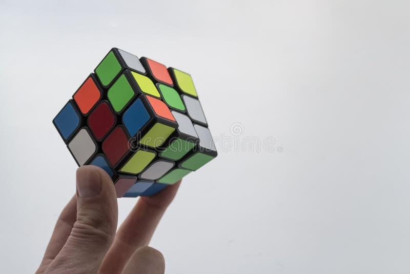 Rubik-` s Würfel in der Kinderhand auf weißem Hintergrund Schließen Sie herauf Foto stockfotos