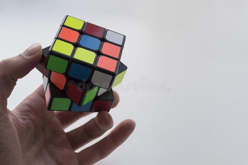 Rubik-` s Würfel in der Mannhand auf weißem Hintergrund Schließen Sie herauf Foto stockfotos