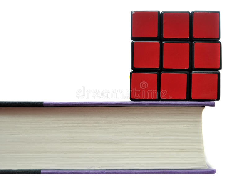 Rubiks Cube on Book. Solved rubiks cube on top of thick book isolated on white background royalty free stock images