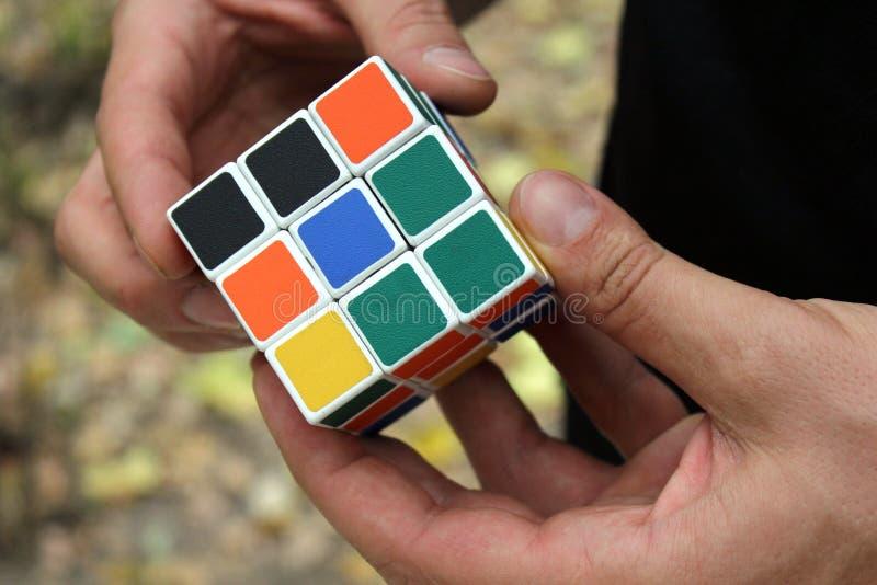 Rubiks kub i hans händer arkivbilder