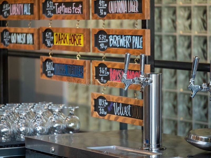 Rubinetti della birra e tipi d'argento di birre all'ancora che fa società fotografia stock libera da diritti
