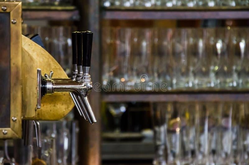 Rubinetti e scaffali della birra con i vetri di birra immagine stock