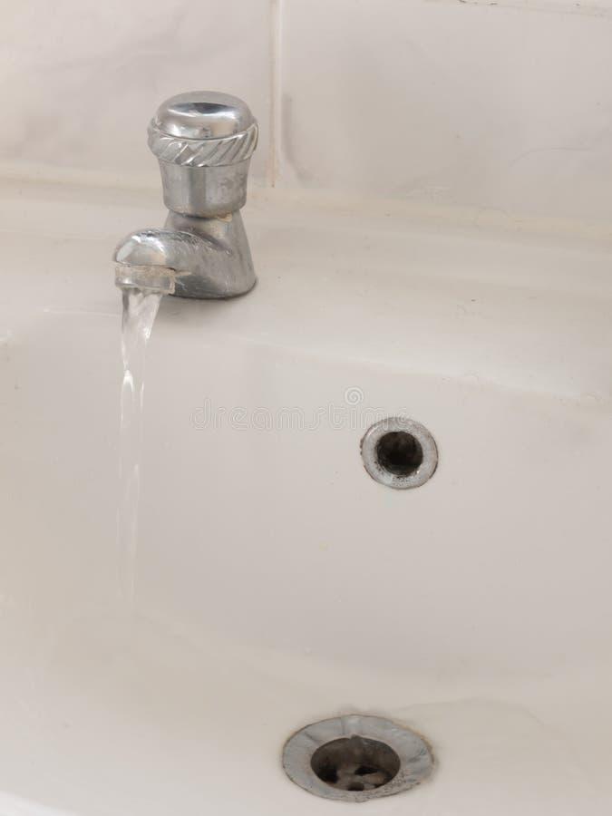 Rubinetto del metallo del bacino del lavandino girato sulla fine dell'acqua su immagine stock