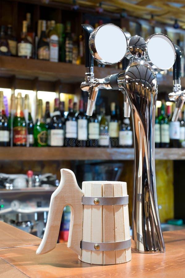 Rubinetto della birra con una tazza in una barra fotografia stock