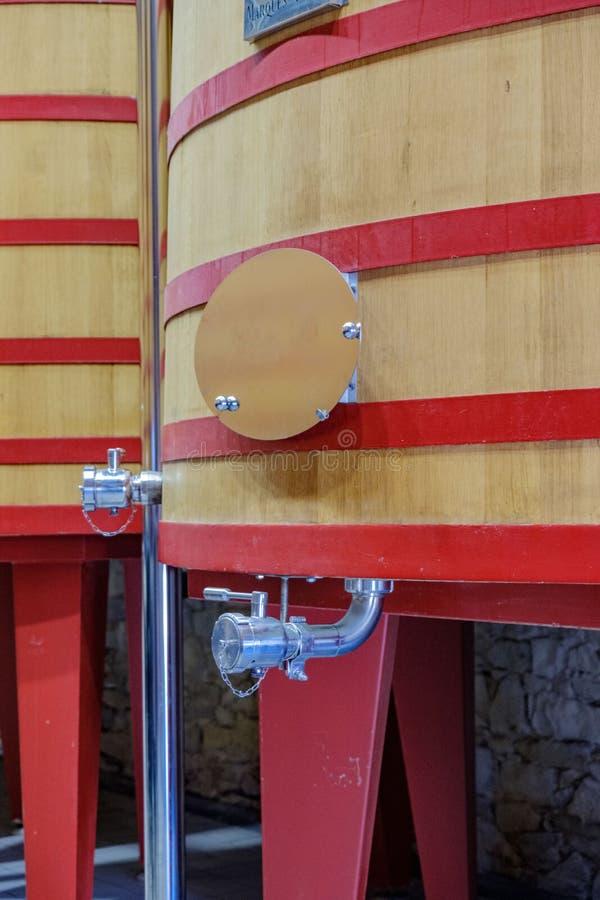 Rubinetto e parte della struttura di grande barilotto in cui comincia fermentare il vino dell'uva per diventare fotografie stock libere da diritti