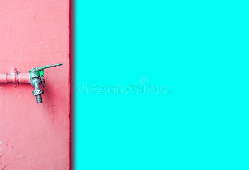 Rubinetto sul rosa della parete e sulla parete blu dell'acqua fotografia stock