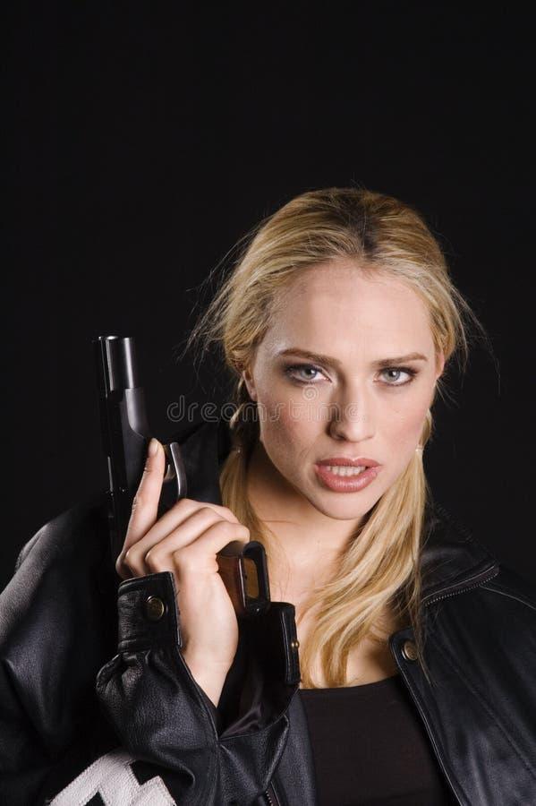 Rubio atractivo con el arma en la chaqueta de cuero imagenes de archivo