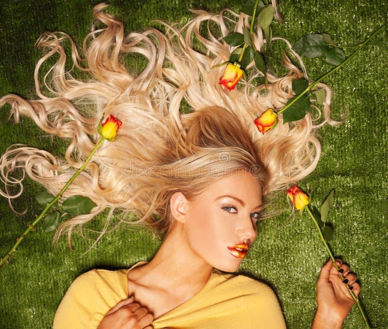 Rubio atractivo con su pelo cubierto en rosas imagen de archivo libre de regalías
