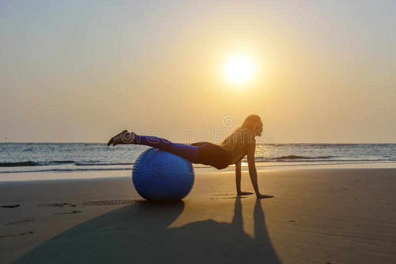 Rubio con el pelo largo hace Pilates en la playa durante puesta del sol contra el mar Mujer feliz flexible joven que hace ejercic imagen de archivo