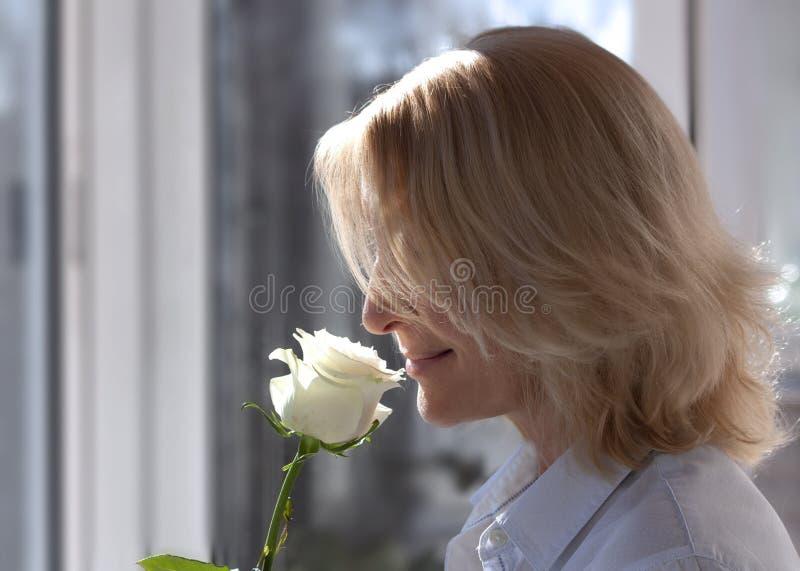 Rubio de mediana edad con el primer color de rosa blanco de la flor fotografía de archivo libre de regalías