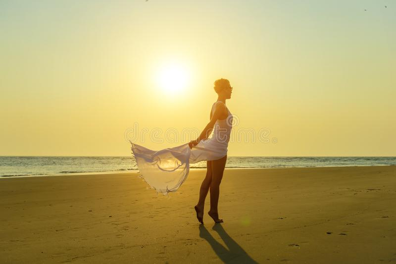 Rubio elegante atractivo en gafas de sol y vestido blanco ligero se coloca descalzo en la arena amarilla en el fondo del mar y de fotografía de archivo