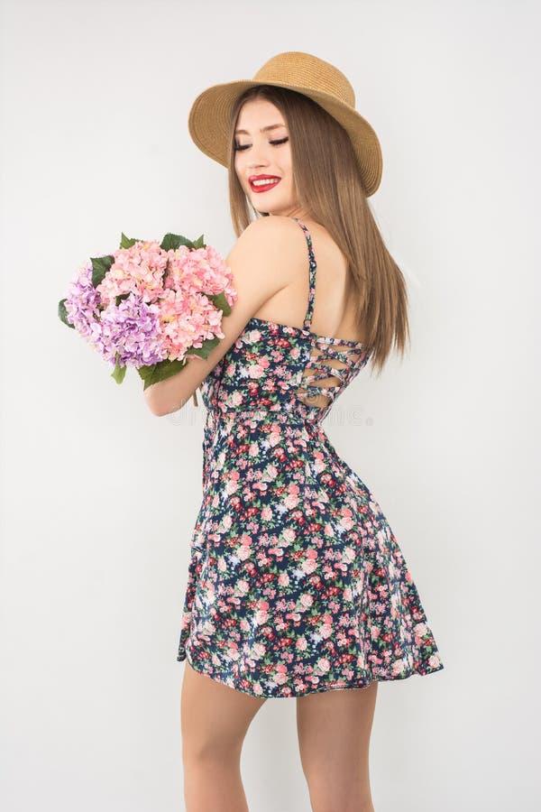 Rubio en un sombrero y un vestido de paja con un ramo de flores imagen de archivo libre de regalías
