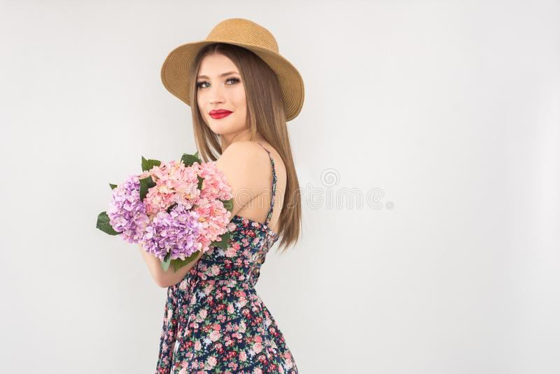 Rubio en un sombrero y un vestido de paja con un ramo de flores fotos de archivo libres de regalías