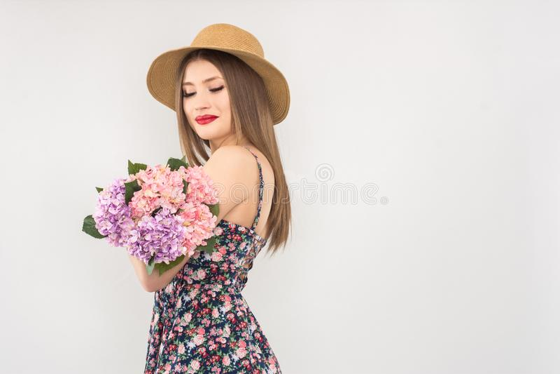 Rubio en un sombrero y un vestido de paja con un ramo de flores fotos de archivo