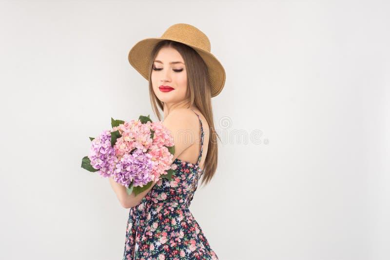 Rubio en un sombrero y un vestido de paja con un ramo de flores imagen de archivo