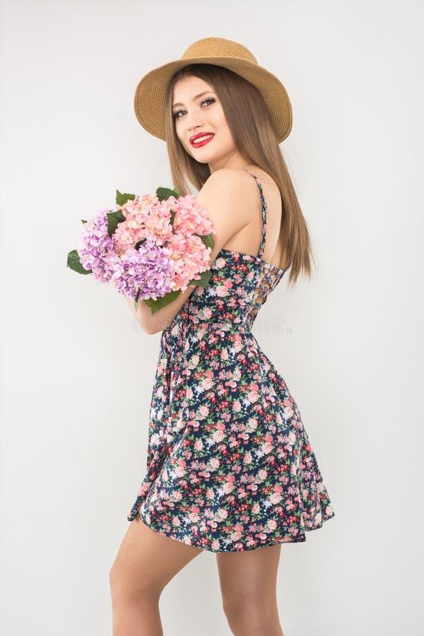 Rubio en un sombrero y un vestido de paja con un ramo de flores imágenes de archivo libres de regalías