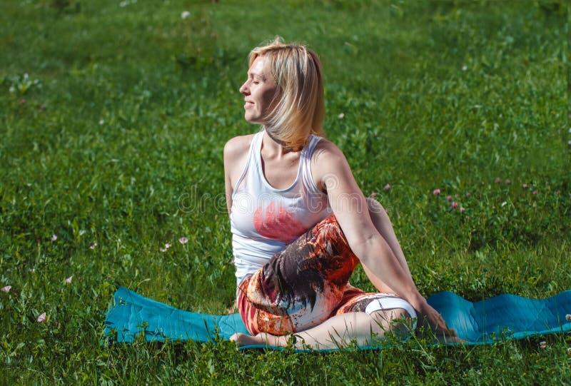 Rubio en una camiseta blanca en la hierba verde que hace yoga Tratamiento y relajaci?n de la espina dorsal Se divierte forma de v foto de archivo