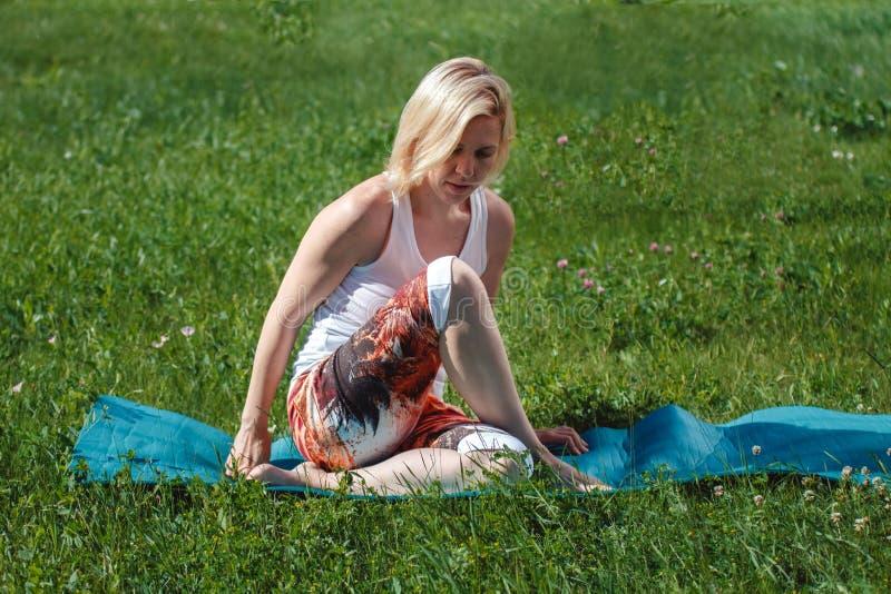 Rubio en una camiseta blanca en la hierba verde que hace yoga Tratamiento y relajaci?n de la espina dorsal Se divierte forma de v fotografía de archivo